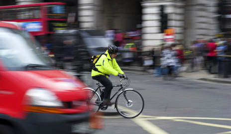 Man cycling in busy London traffic