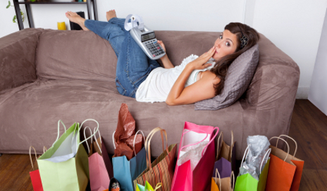 Woman with calculator and lots of shopping bags