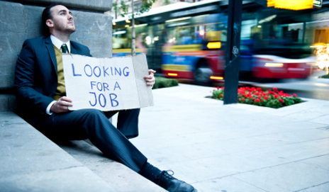 Young businessman holding sign 'Looking for a job'