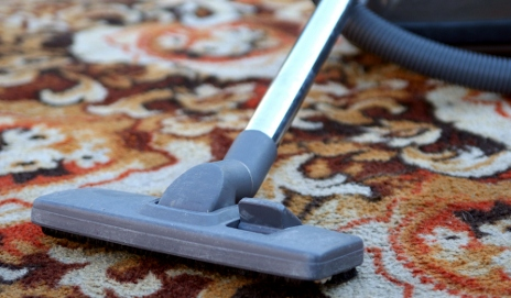 Old vacuum cleaner on retro carpet