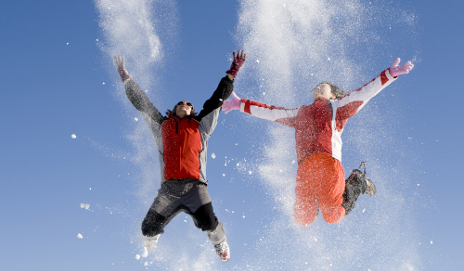 Two skiers jumping for joy