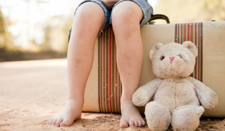 Girl sat on suitcase with battered teddy bear
