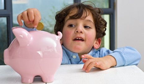 Child reaching into piggy bank