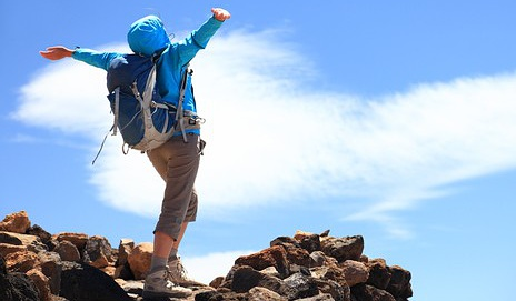 Happy woman hiker reaching her goal at the mountain top summit