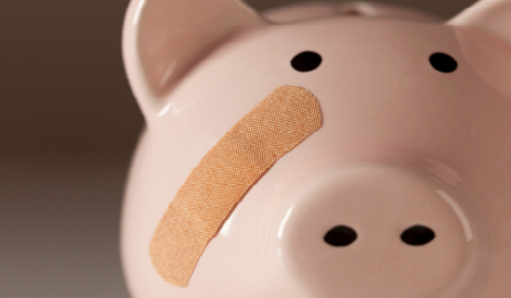 Piggy bank with plaster on face
