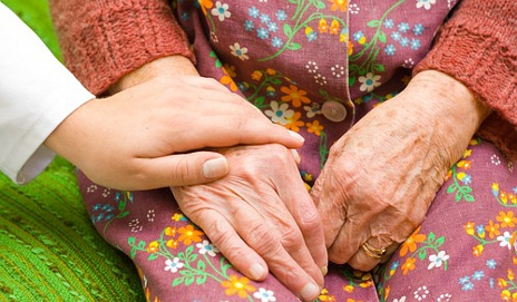 Carer holding hands with an older person
