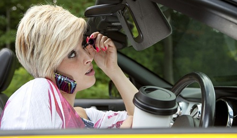 Distracted female driver on phone, applying make-up