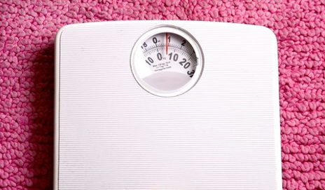Weighing scales on pink background