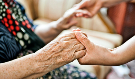 Older person's hands being held