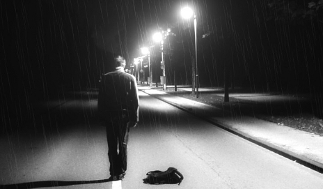 Man walking along a dimly lit road