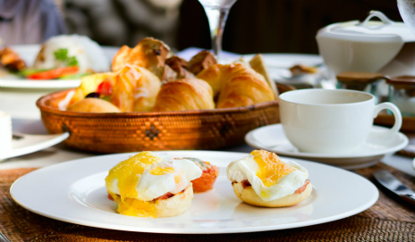 A hotel breakfast with eggs, croissants and hot drinks