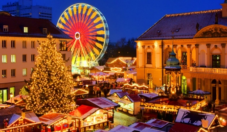 European Christmas market at night with Christmas tree and ferris wheel