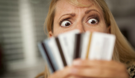 Woman looking in fear at her credit cards