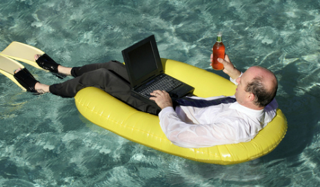 Man in a swimming pool using a laptop