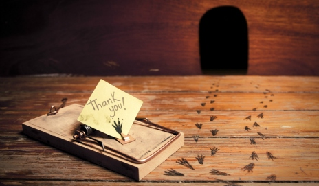 An empty mousetrap outside a mouse hole with tiny footprints leading away
