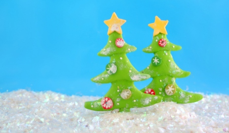 Two clay Christmas trees in an artificial snowy landscape