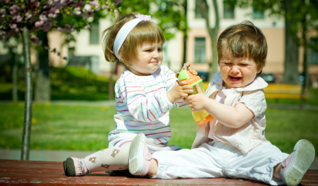 Two children fighting over a bottle of juice
