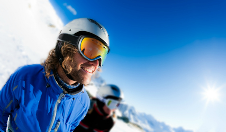 Smiling man wearing ski helmet and goggles, with a snowy mountain in the background