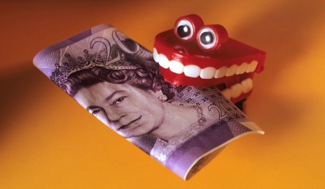 False teeth gripping onto a twenty pound note