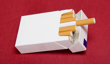 Plain cigarette packet against red background