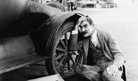 Black and white photo of man next to broken down car