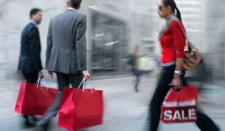 Two men and a woman walking with red shopping bags