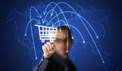 Man standing behind a transparent world map, pointing his finger at a shopping trolley in the middle of the map