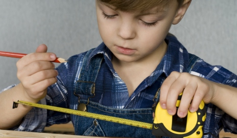 Small boy with a measuring tape and pencil