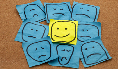 Blue post-it notes with sad faces drawn on