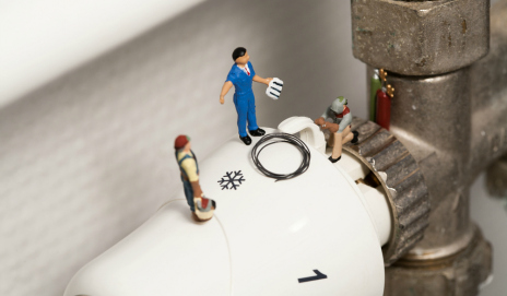 Some tiny plumbers fixing a radiator thermostat