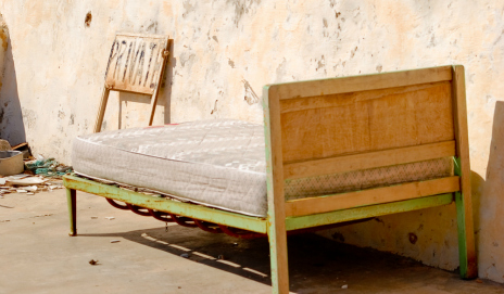 An old bed outside a building