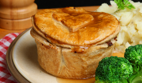 A steak pie with mash and veggies