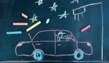 A chalk drawing of a car on a blackboard