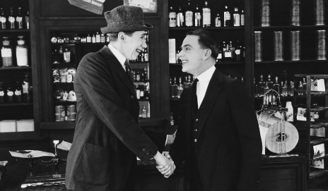 Men shaking hands in shop, black and white photo