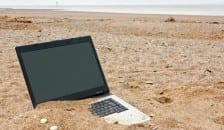A discarded laptop on a beach