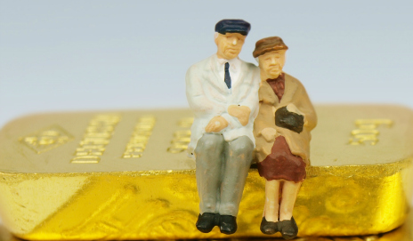 Two old people sat on a bar of gold