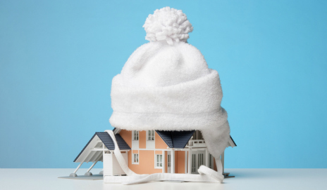 A model house with a bobble hat on the roof