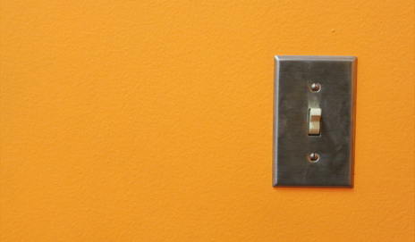 A light switch on an orange wall