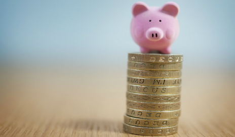 A piggy bank sat on a stack of pound coins