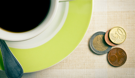Coins next to coffee cup