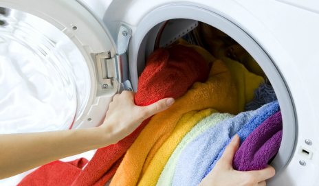 A washing machine with rainbow-coloured laundry