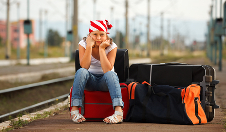 Girl sat on suitcase waiting for train