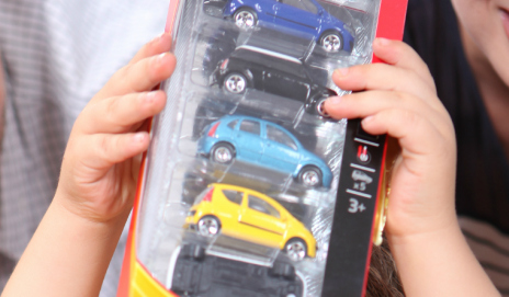 Child holding up car toy