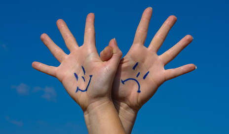 Happy and sad hands against blue background