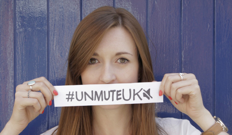 Supporter with the UNMUTEUK hashtag over their mouth