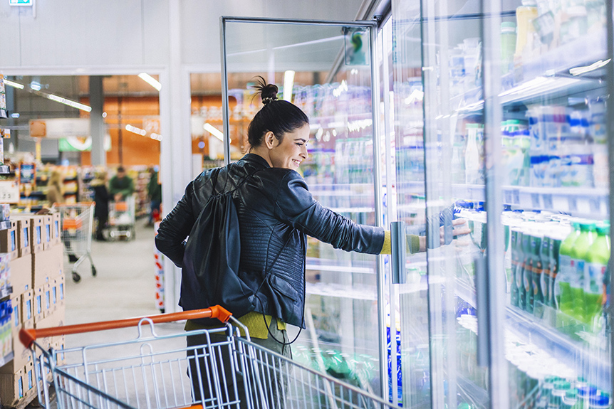 A young woman removes a cold beverage from a supermarket refrigerator