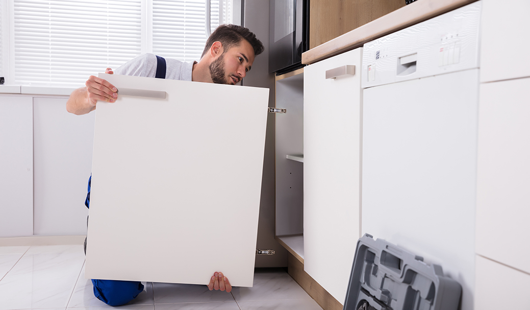 A fitter installs a cabinet door as part of a kitchen installation