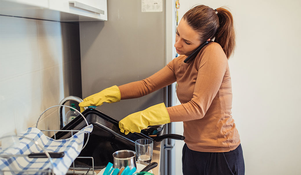 A customer with a broken dishwasher handwashes her dishes while on the phone