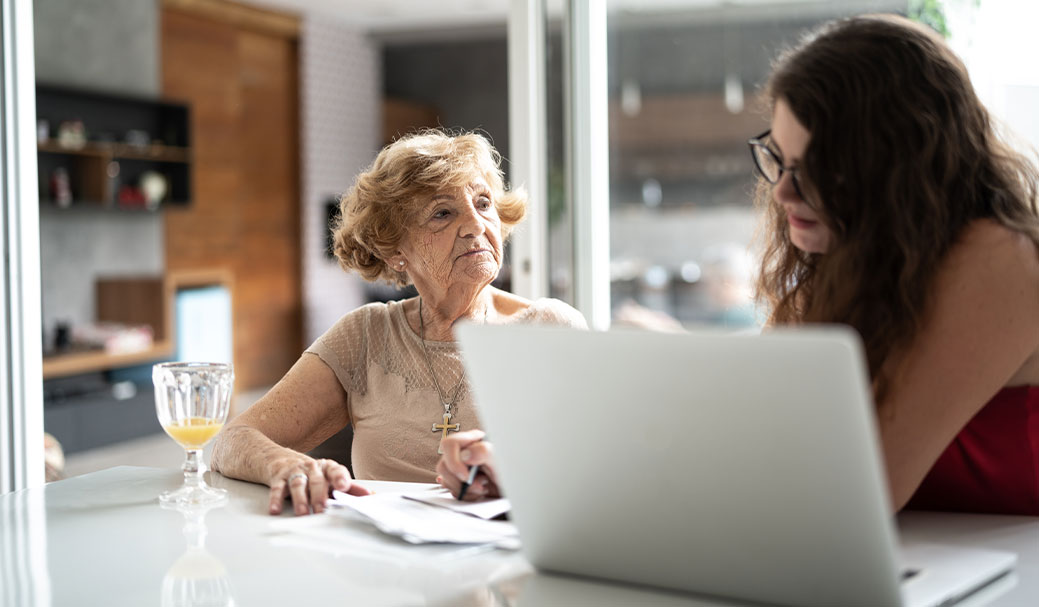 An elderly woman discusses her appliance insurance bill with her daughter
